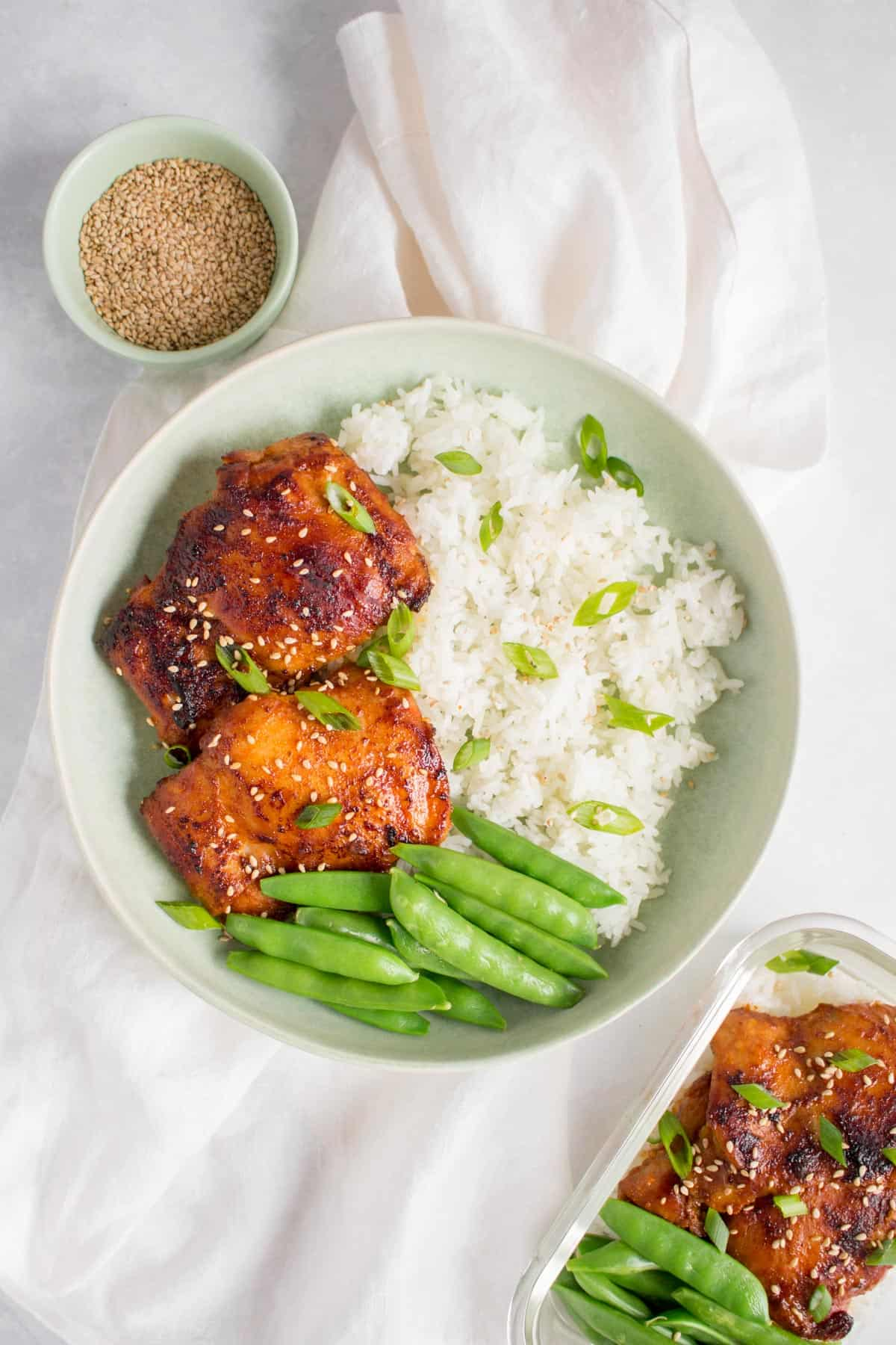A plate of chicken thighs with snap peas and rice.