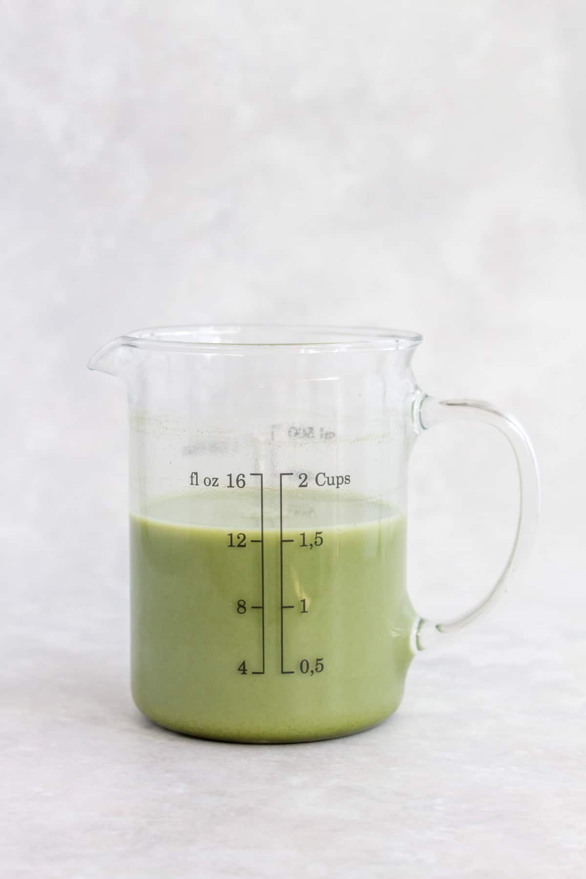 Matcha mixture in a measuring cup.