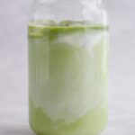 Matcha added to the milk in a glass.
