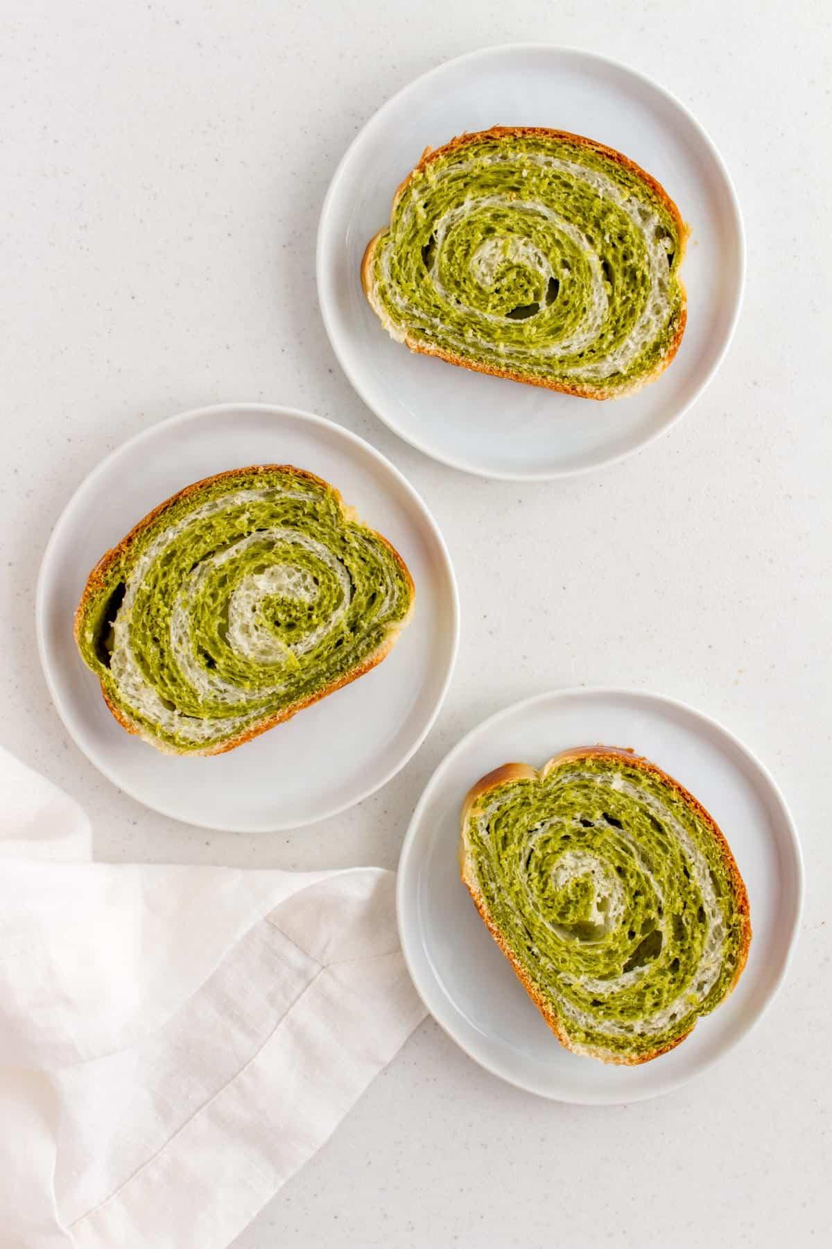 Three slices of matcha bread on mini plates.
