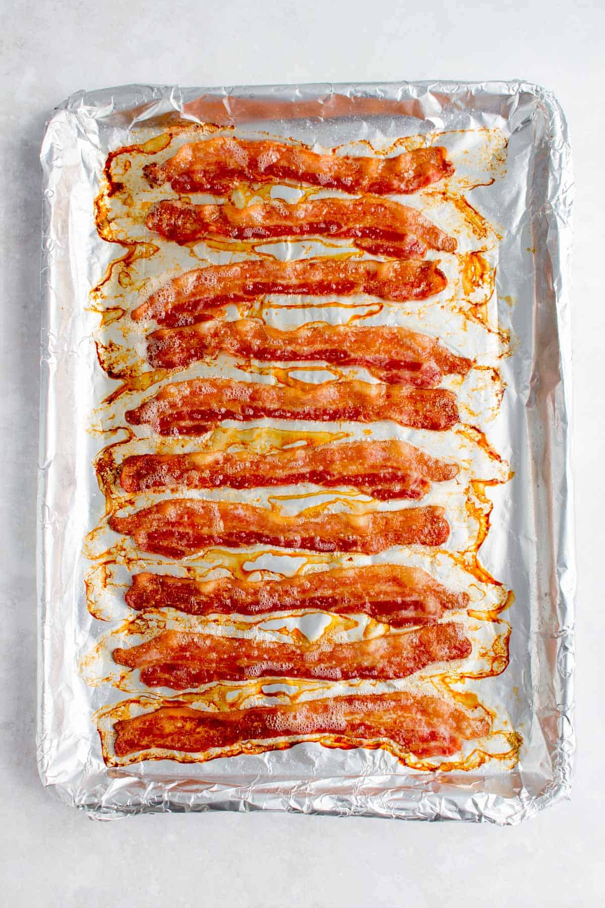 Freshly baked bacon on a sheet pan.