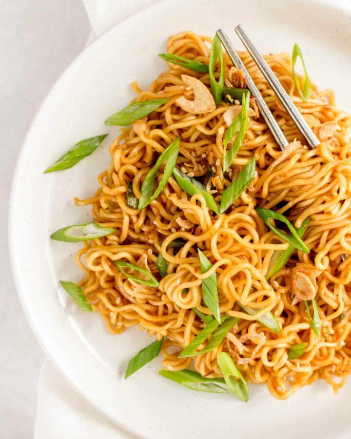 Close up of a plate of sesame noodles with chopsticks.