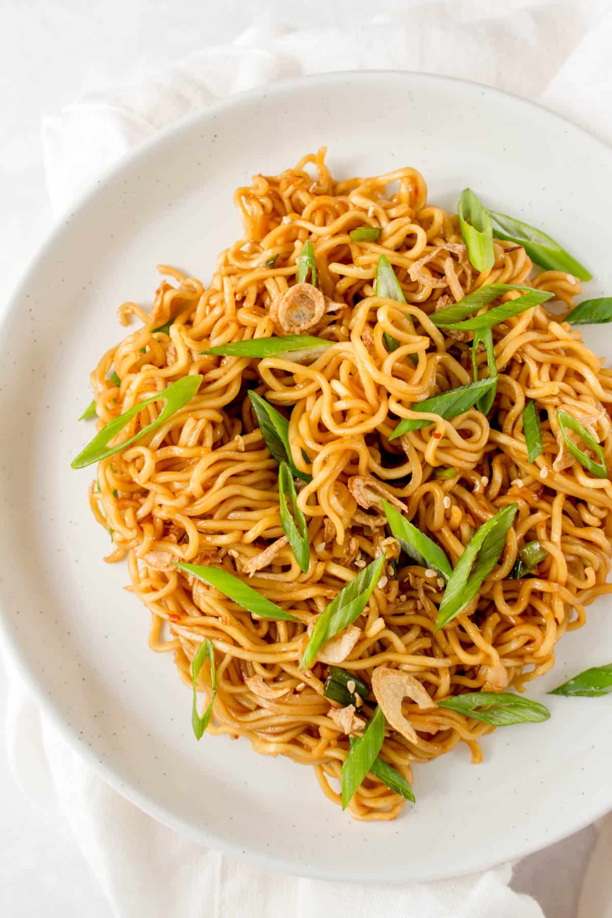 A plate of sesame noodles with green onions.