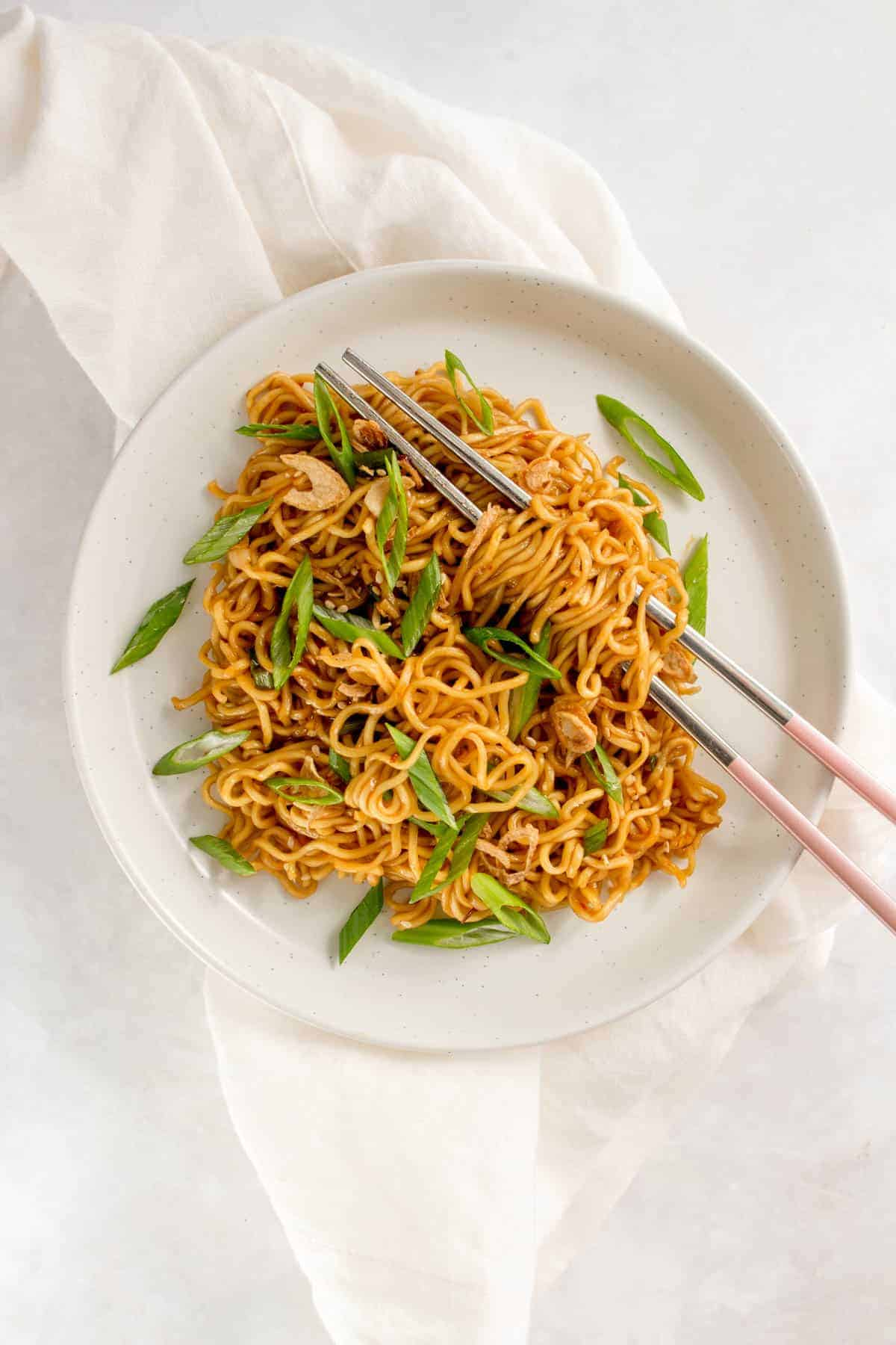 Bowl of sesame noodles topped with green onions and fried onions.