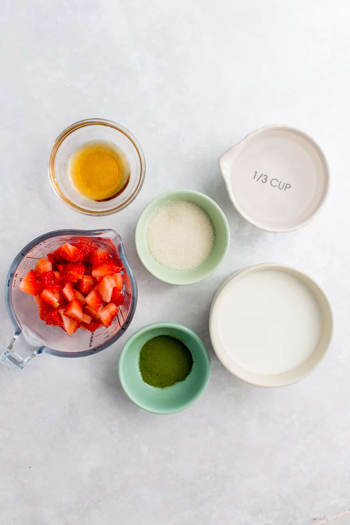 Ingredients needed to make a strawberry matcha latte.