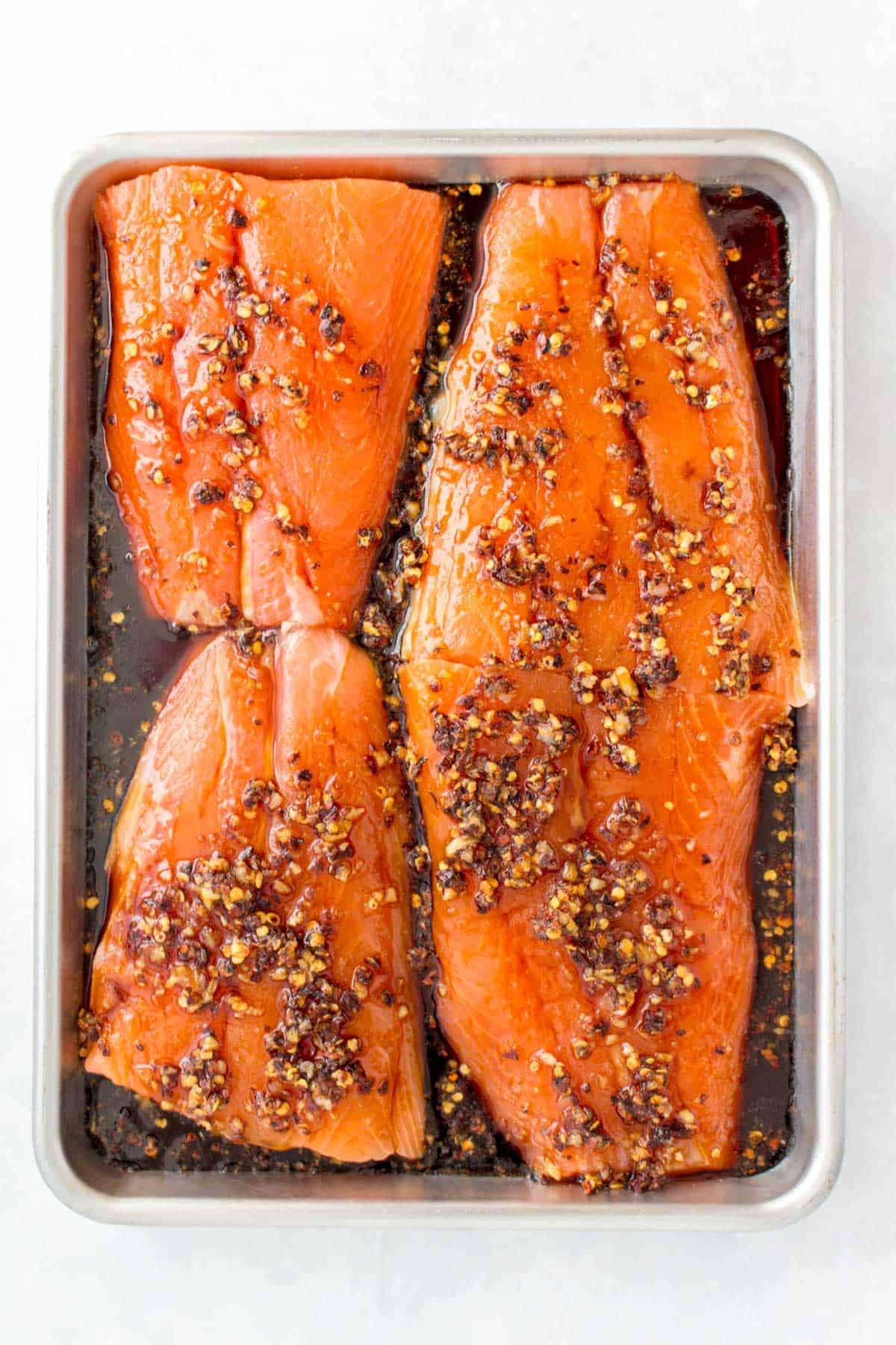 Salmon fillets marinating in a sheet pan.