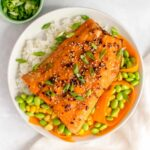 A plate with rice, corn, edamame, carrots, and sweet chili salmon.