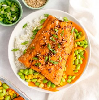 A plate with rice, corn, edamame, carrots, and sweet chili salmon on top.