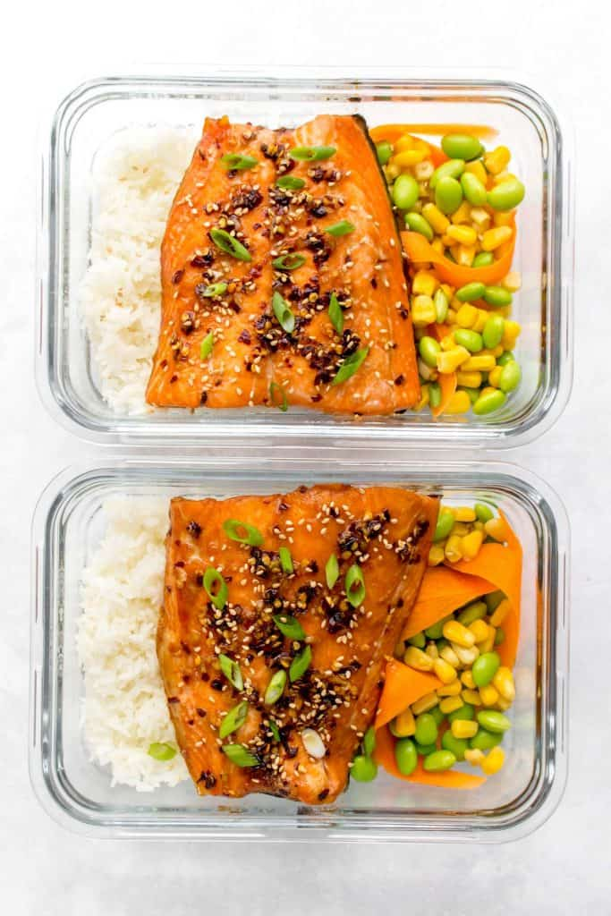 Two meal prep containers with sweet chili salmon and rice, corn, edamame, and carrots.
