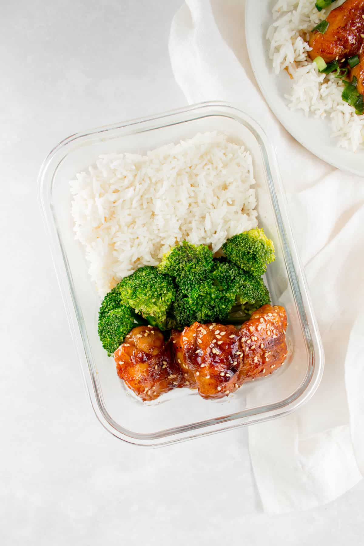 Meal prep container with orange honey glazed chicken thighs with broccoli and rice.