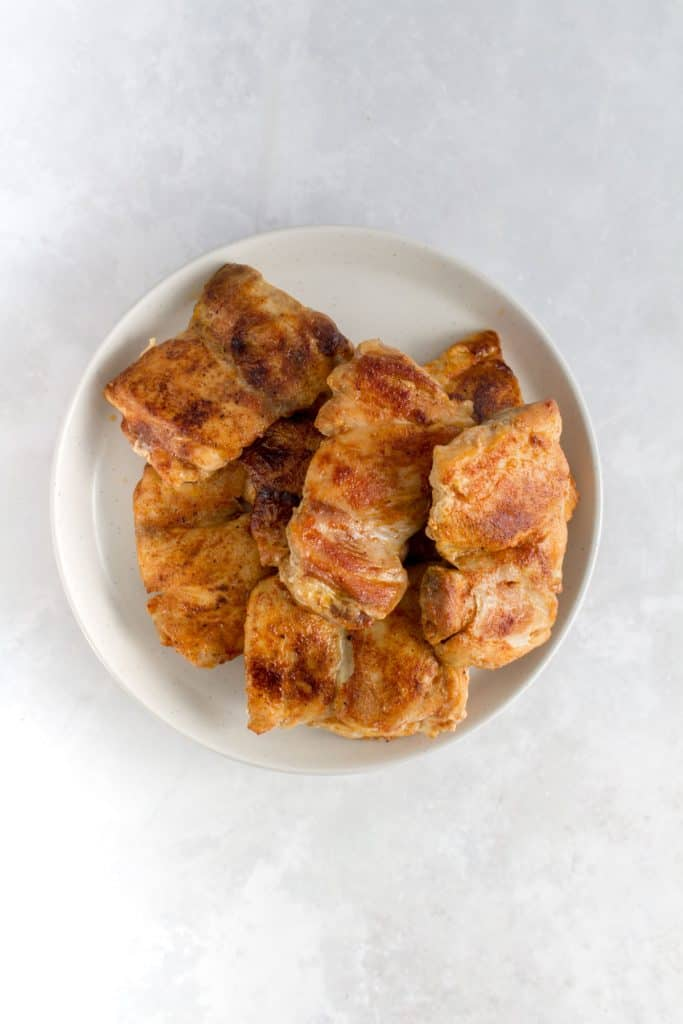 Pan seared chicken thighs on a plate.
