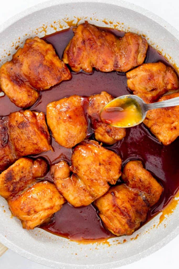 Close up of chicken being coated in orange honey glaze in a skillet.