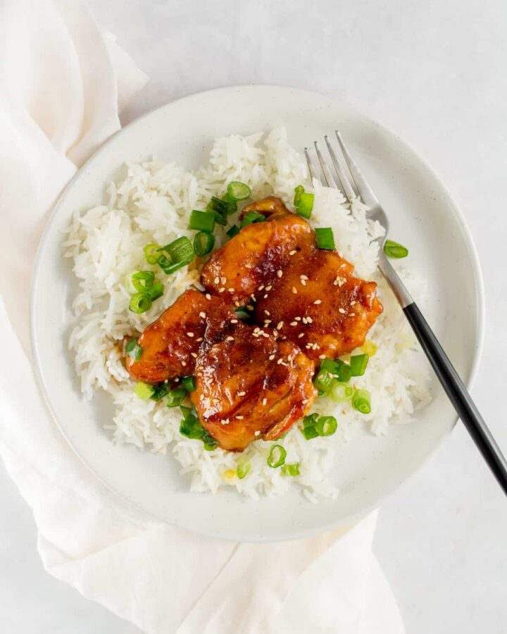A plate with a bed of rice with green onions with two orange glazed chicken thighs on top.