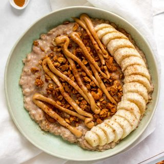 A plate of banana bread oatmeal with sliced bananas, granola, and nut butter.