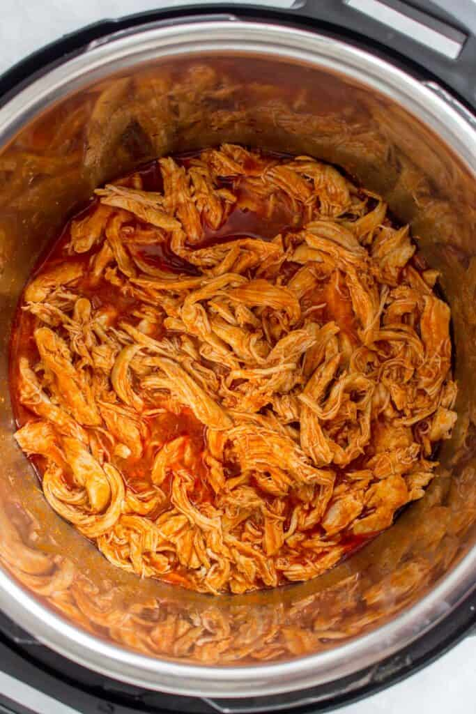 Close up of shredded chicken with buffalo sauce.