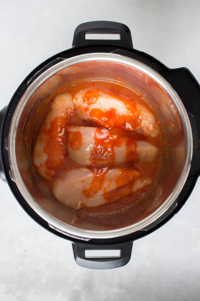 Coating chicken with more Buffalo sauce and a splash of liquid.