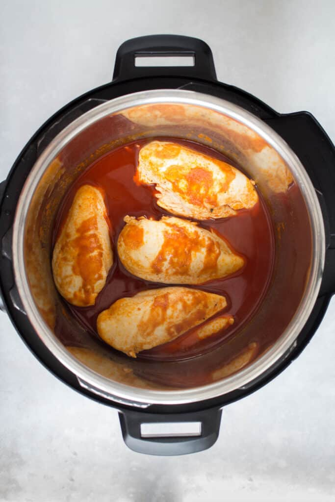 Cooked buffalo chicken in a pressure cooker.