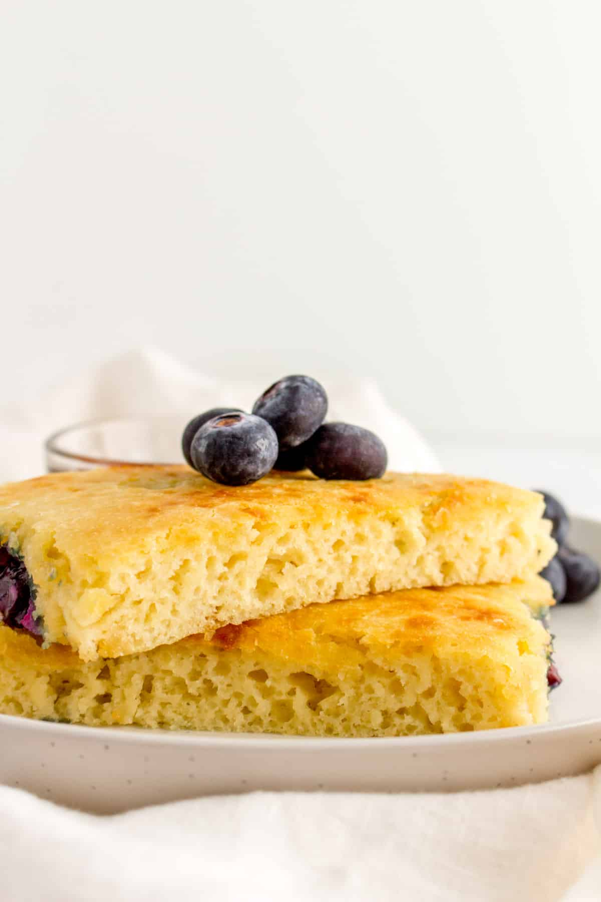 A stack of two sheet pan pancakes with blueberries on top.