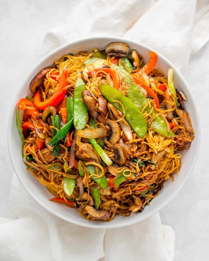 A large plate of soy sauce pan fried noodles with vegetables.