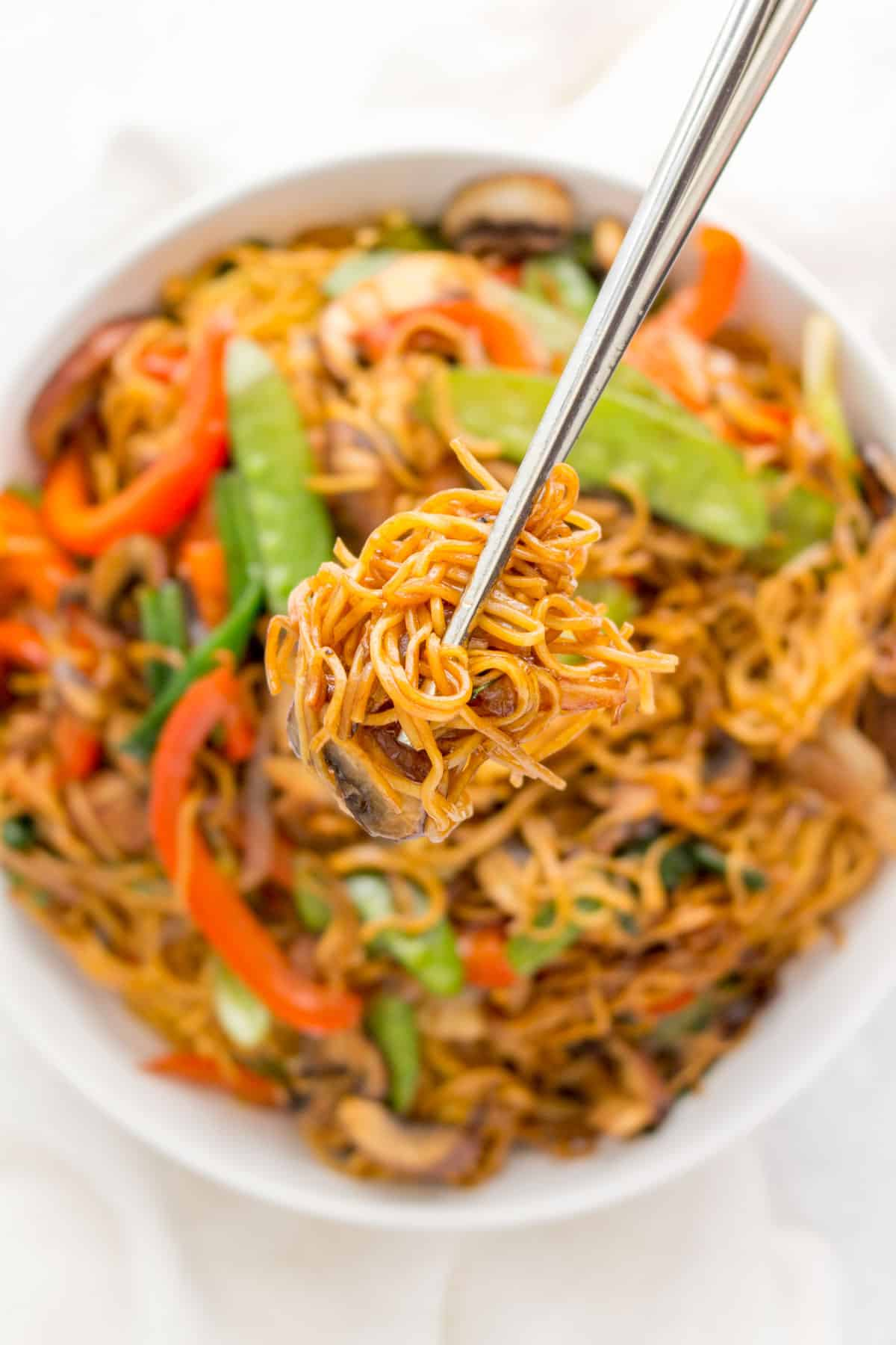 Chopsticks holding up noodles.