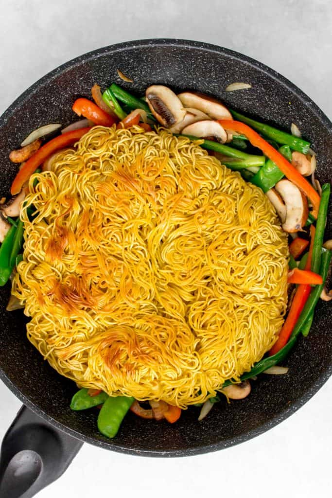 Fried noodles added back to a pan.