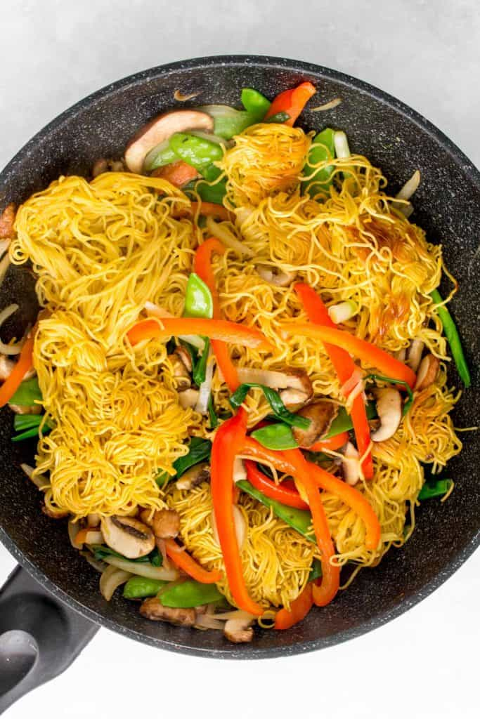 Noodles mixed into vegetables in a pan.