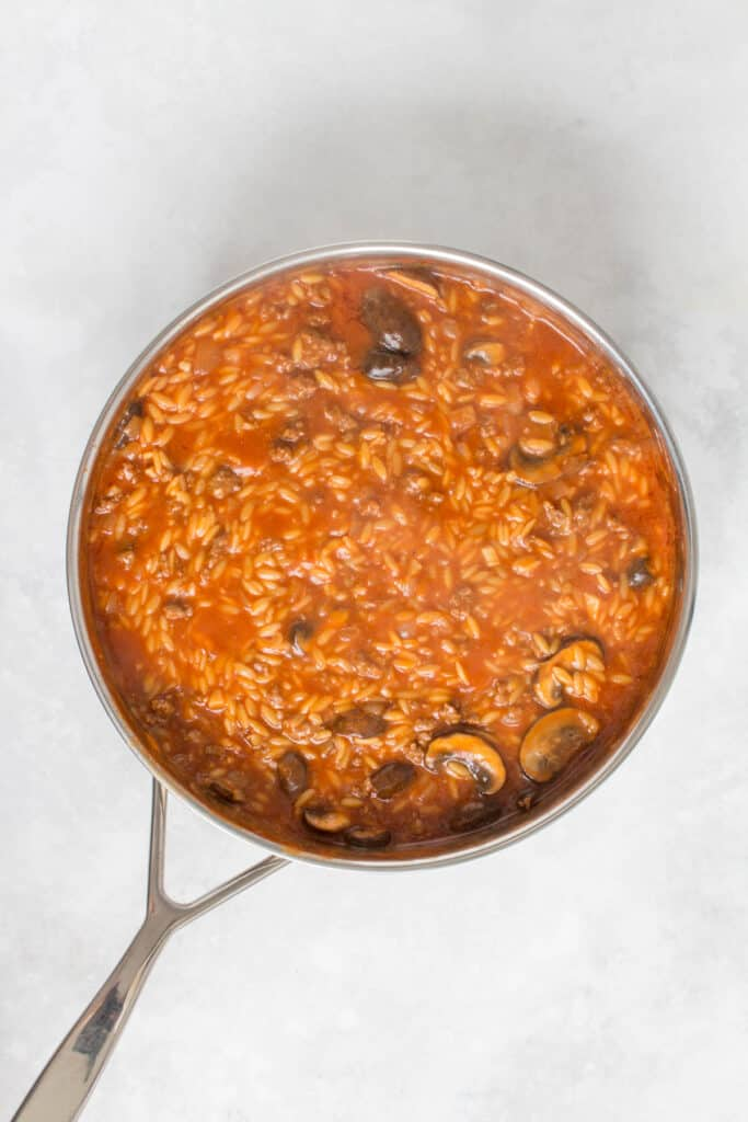 Cooked orzo in a tomato beef sauce.