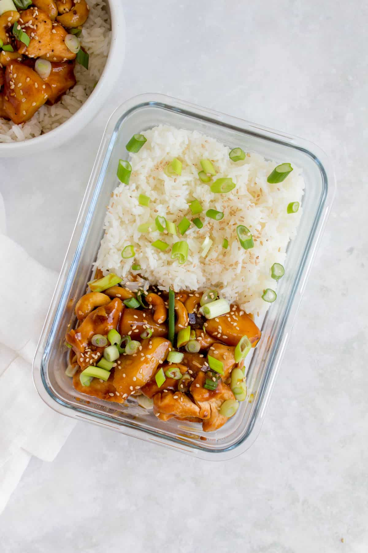 A glass meal prep container with rice and pineapple chicken.
