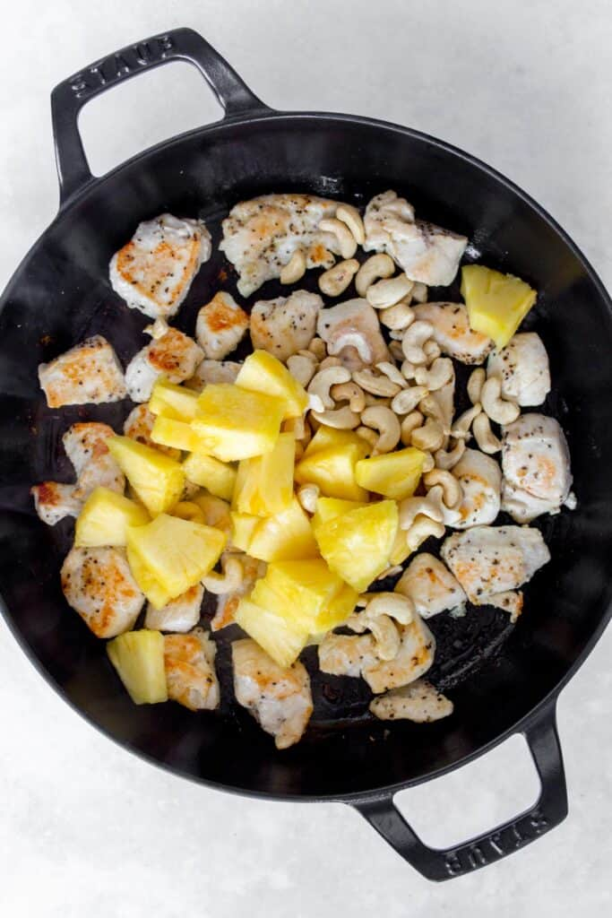 Cashews and pineapples added to a pan with chicken.