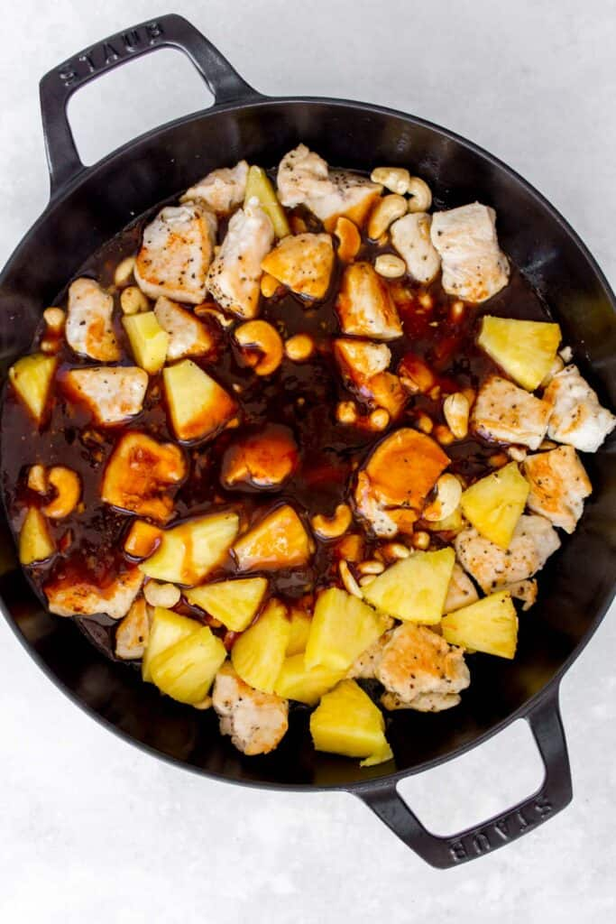 Sauce added to a pan with pineapple, cashews, and chicken.
