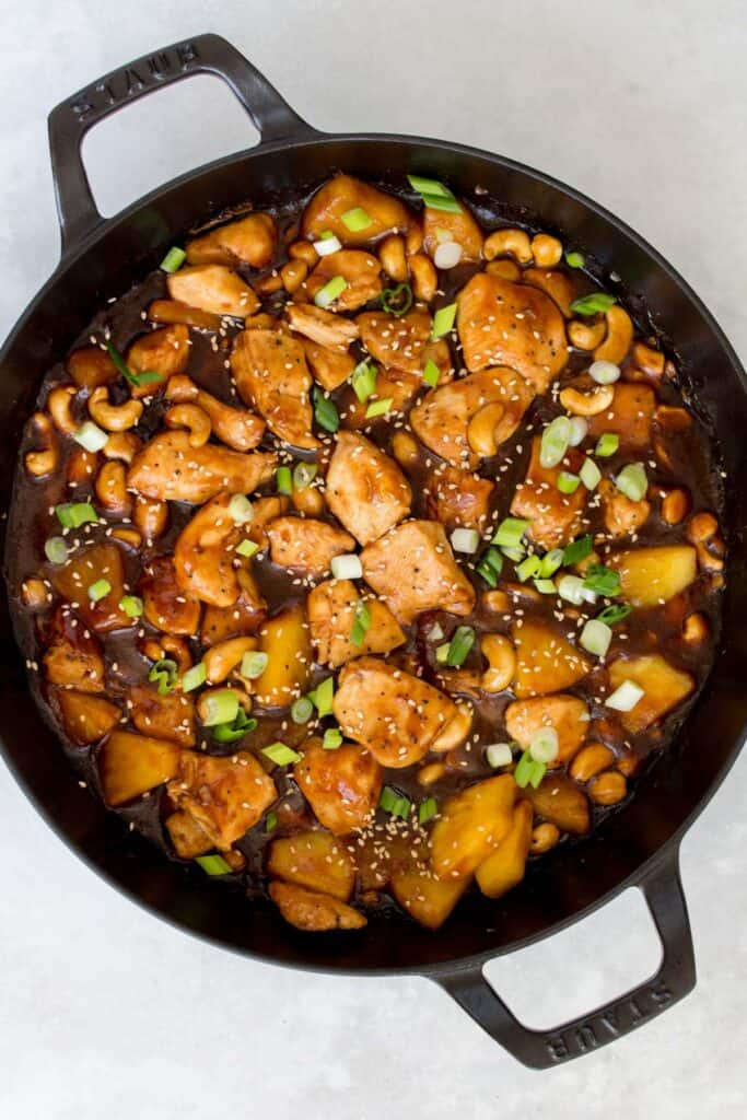 Pineapple chicken in a Staub with green onions and sesame seeds.