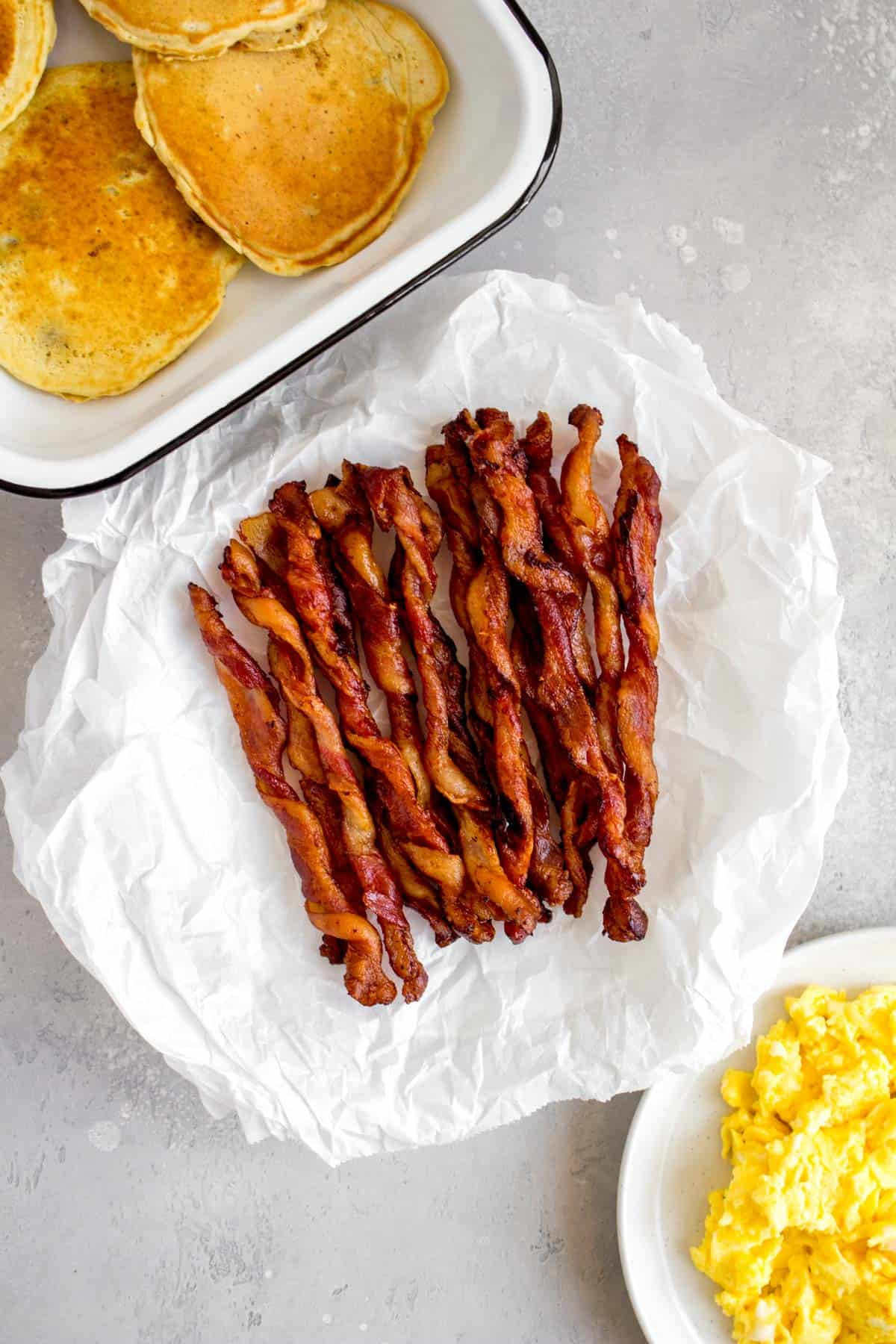 Overhead view of a platter of twisted bacon beside some pancakes and eggs.