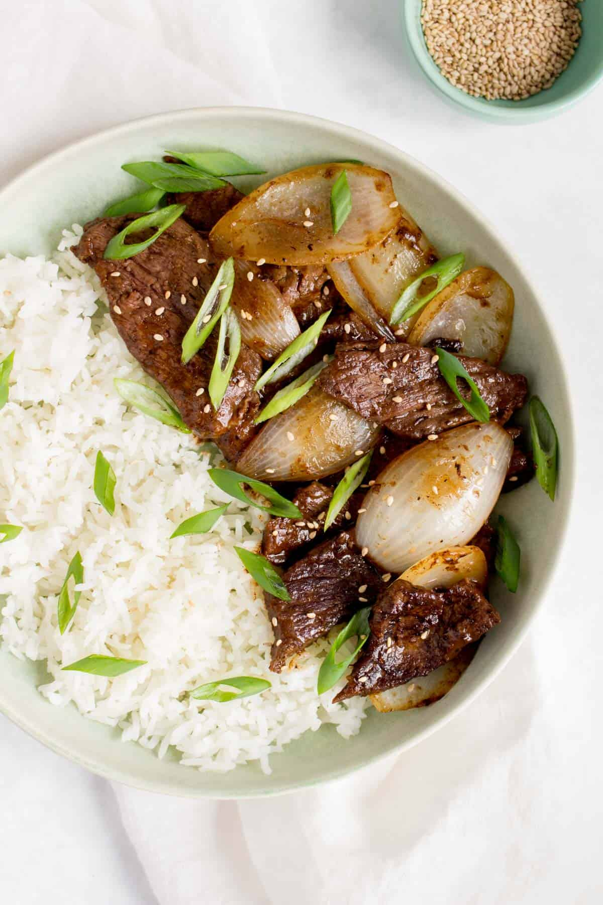Close up of a bowl of rice with beef and onions stir fry.