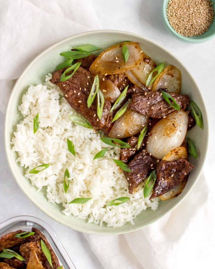 A bowl of rice with beef and onion stir fry with green onions on top.