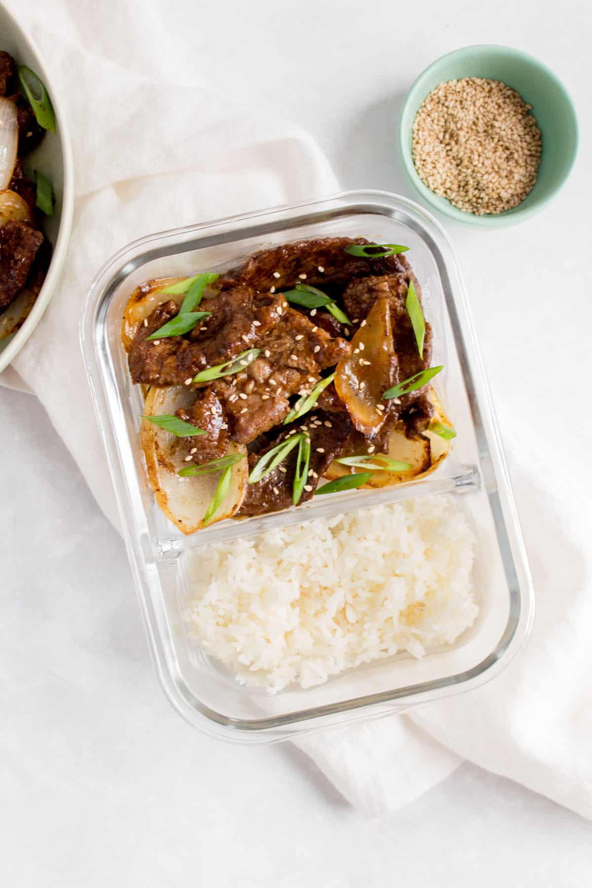 A meal prep container with two compartments with rice in one and beef and onions in the other.