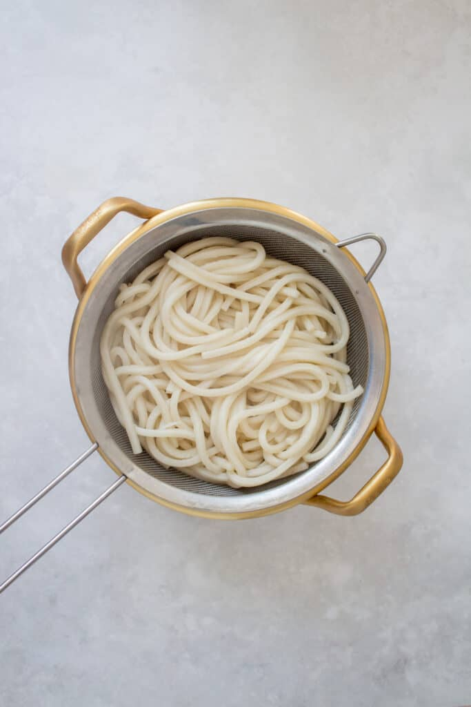 Udon noodles in a strainer.