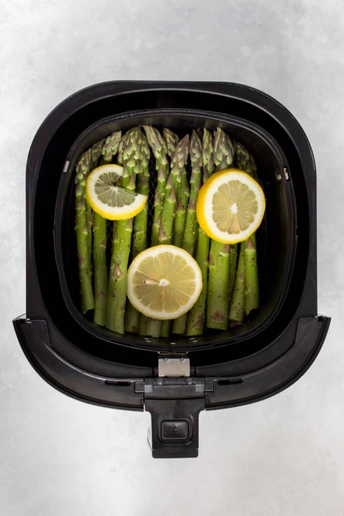 Air fryer asparagus with lemon slices in the basket.