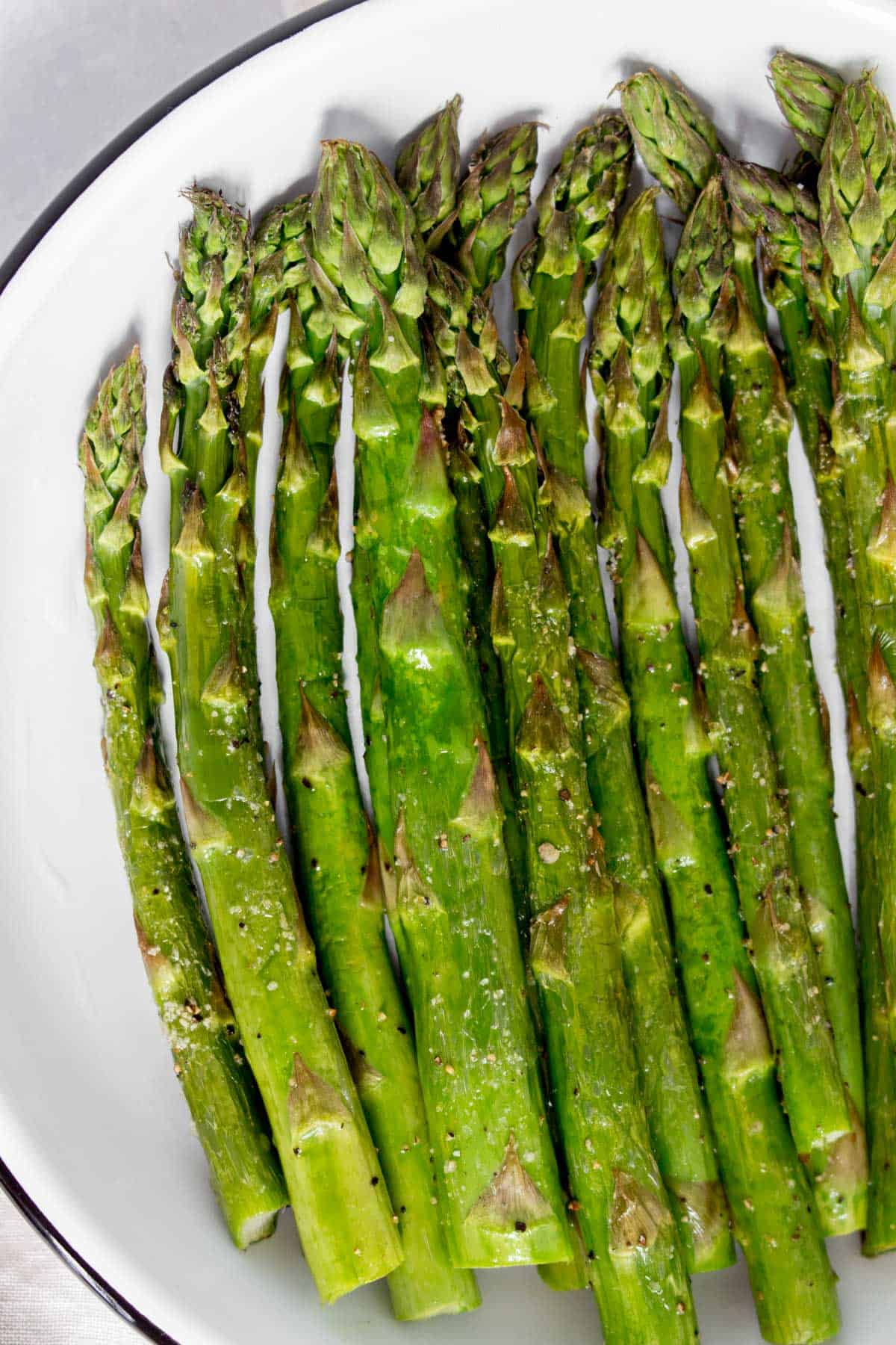 Close up of air fried asparagus on a plate.