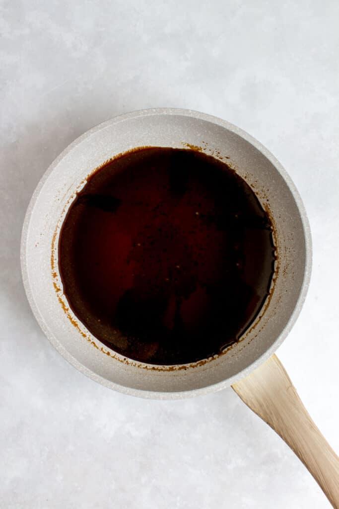Making dakgangjeong (soy garlic glaze) in a pan.