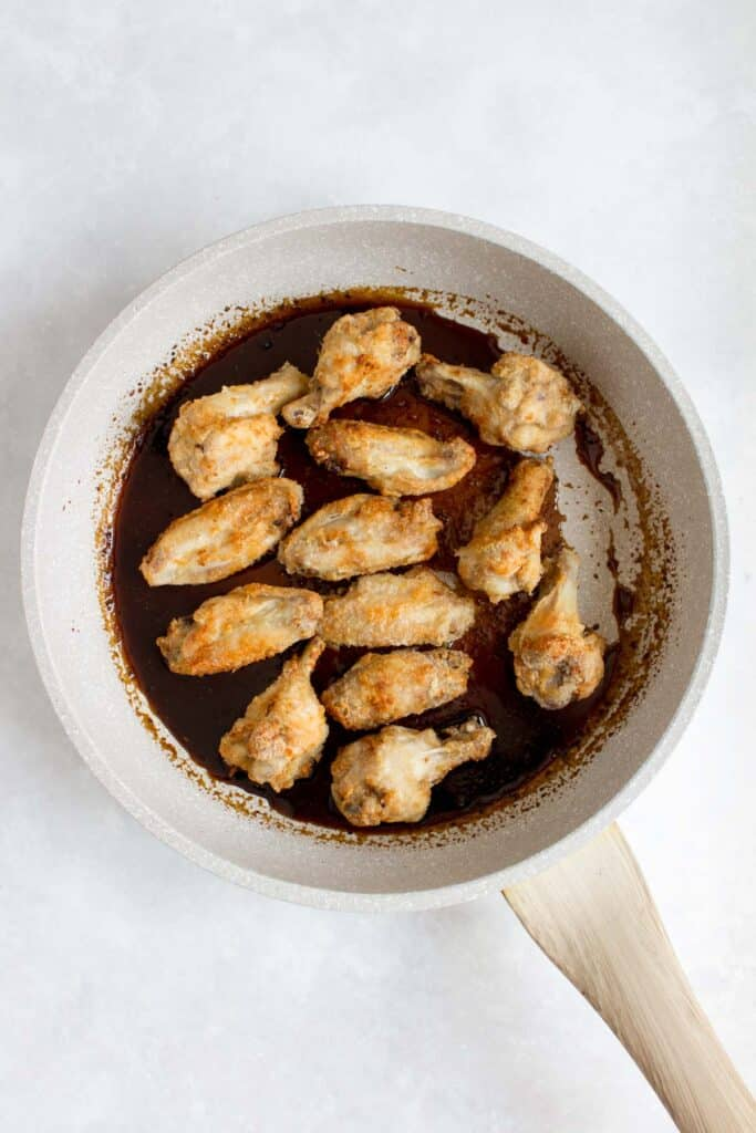 Chicken wings being coated in soy garlic glaze (dakgangjeong).