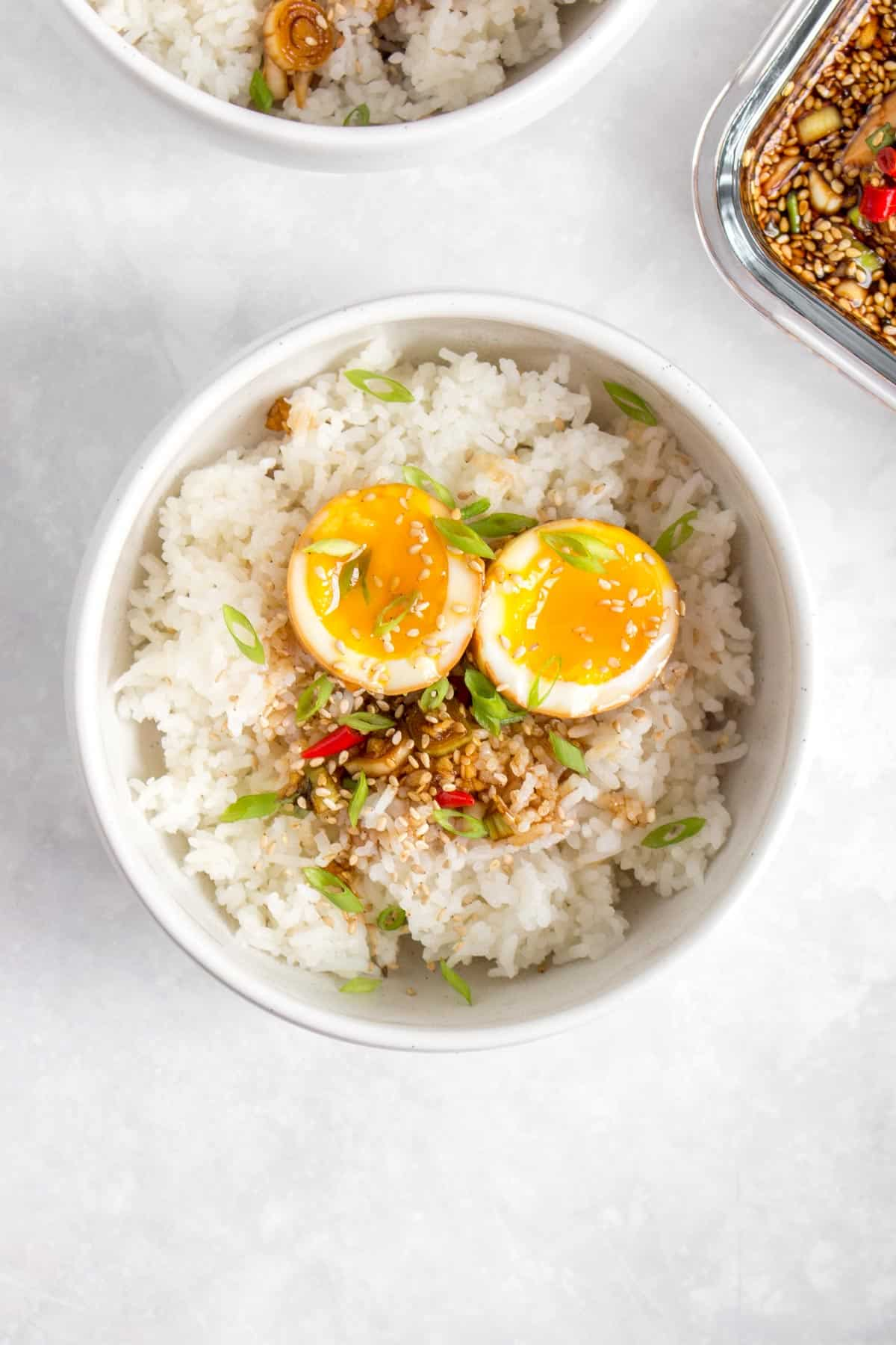 Overhead view of a bowl of rice with Korean marinated egg.