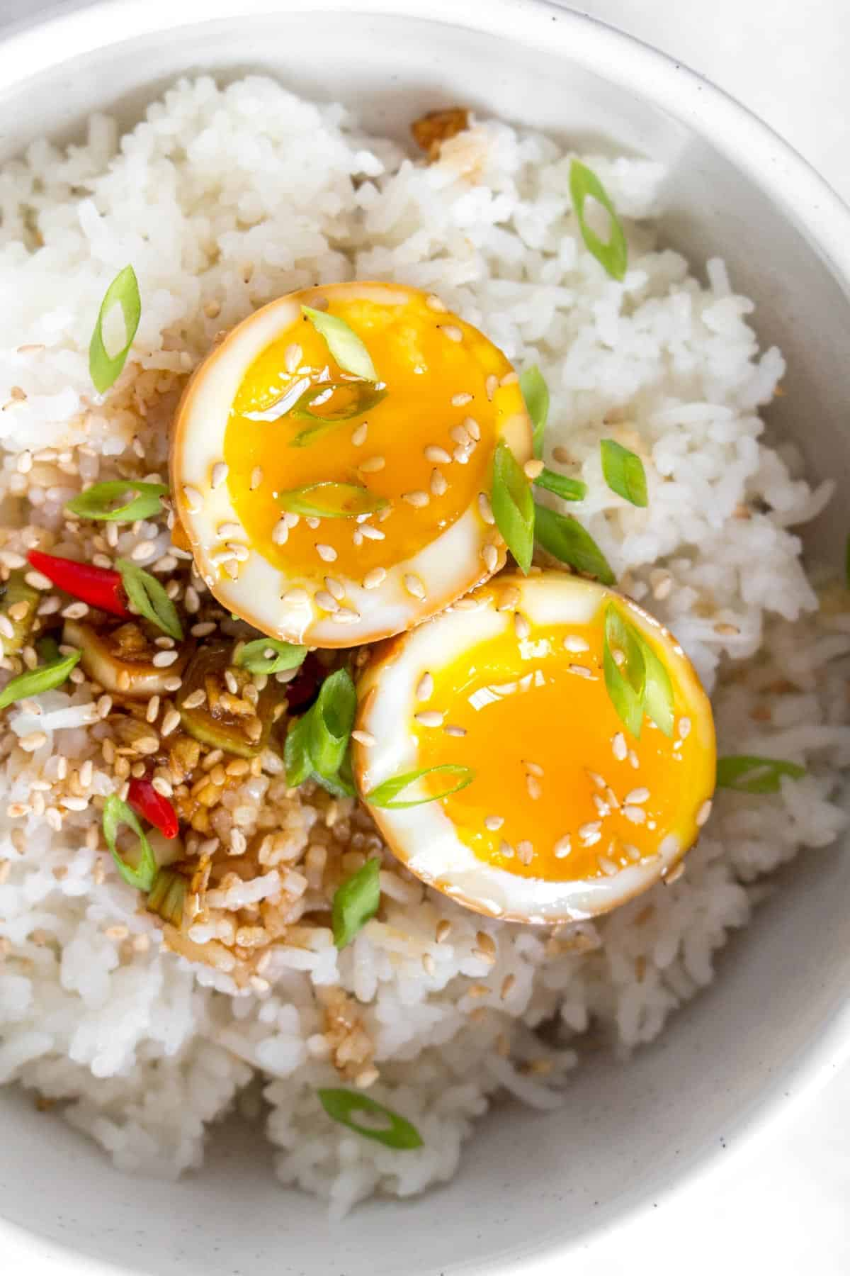 Close up of a Korean marinaded egg, cut in half, in a bowl of rice.