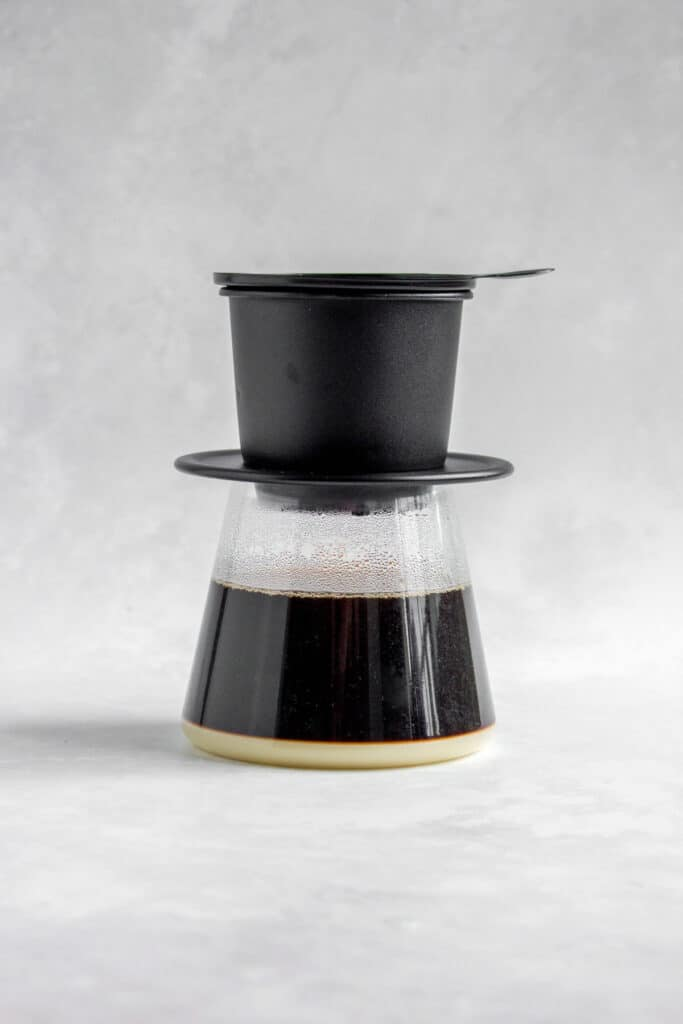 Glass with a Vietnamese coffee phin on top and coffee dripping in.