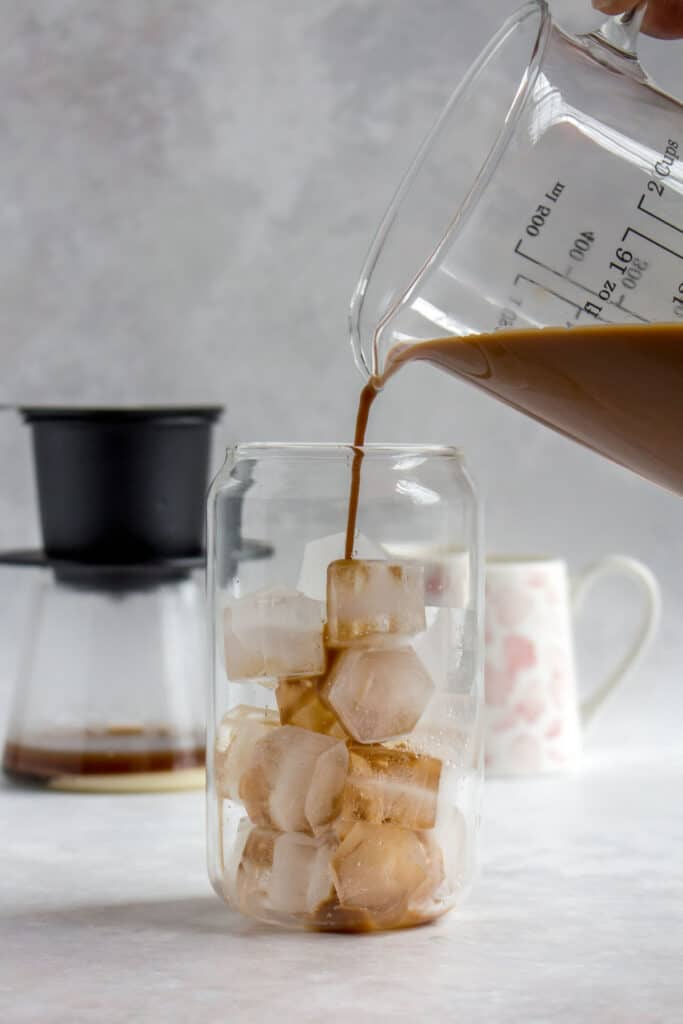 A glass of Vietnamese coffee being poured into a glass of ice.