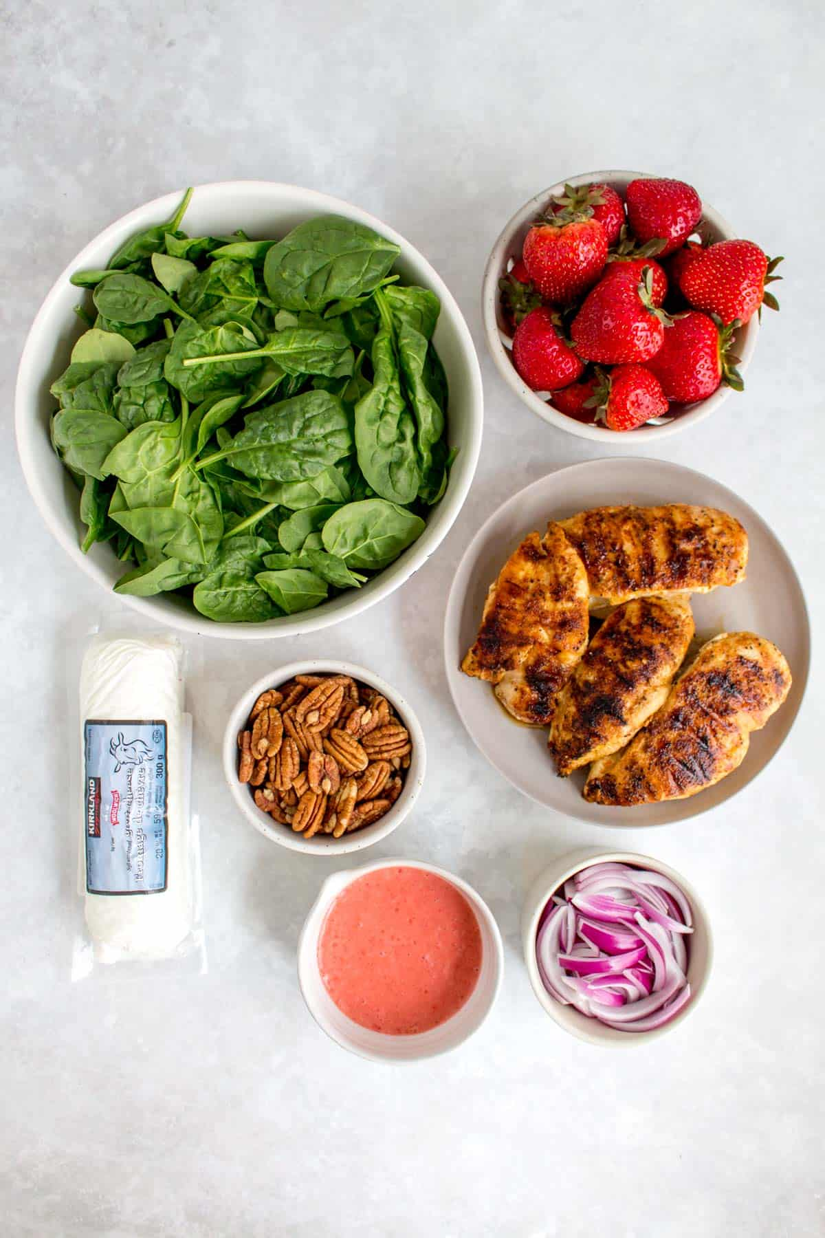 Ingredients needed to make strawberry spinach salad.