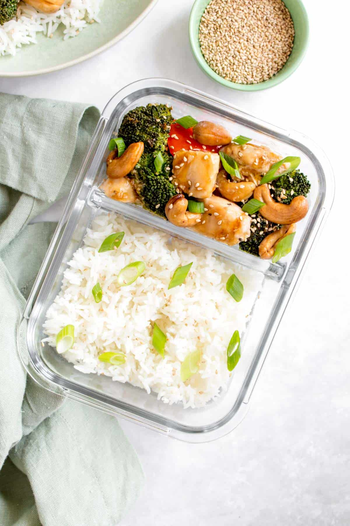 Meal prep container with rice on one side and cashew chicken on the other.