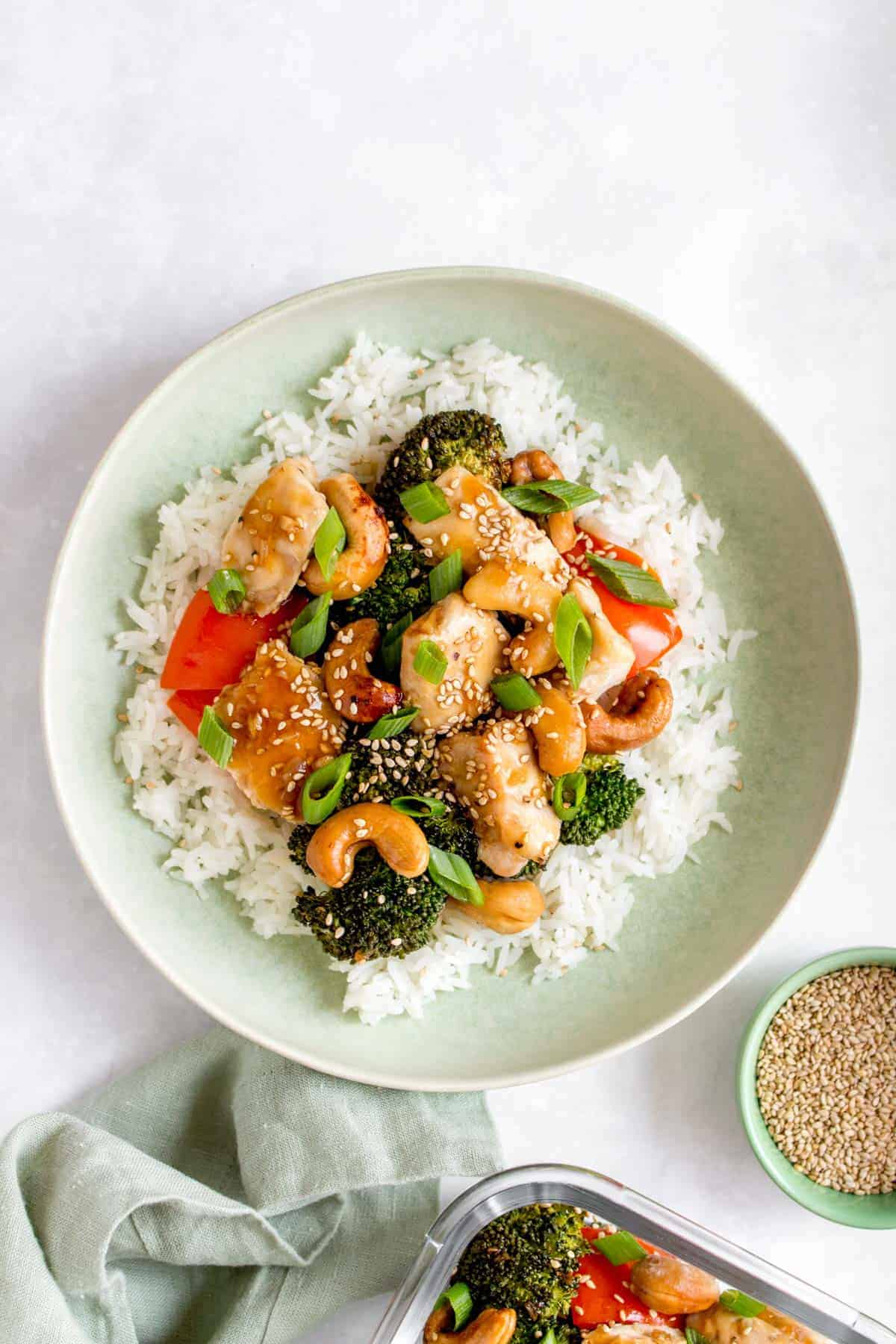 Sheet pan cashew chicken over a bed of rice in a green plate.
