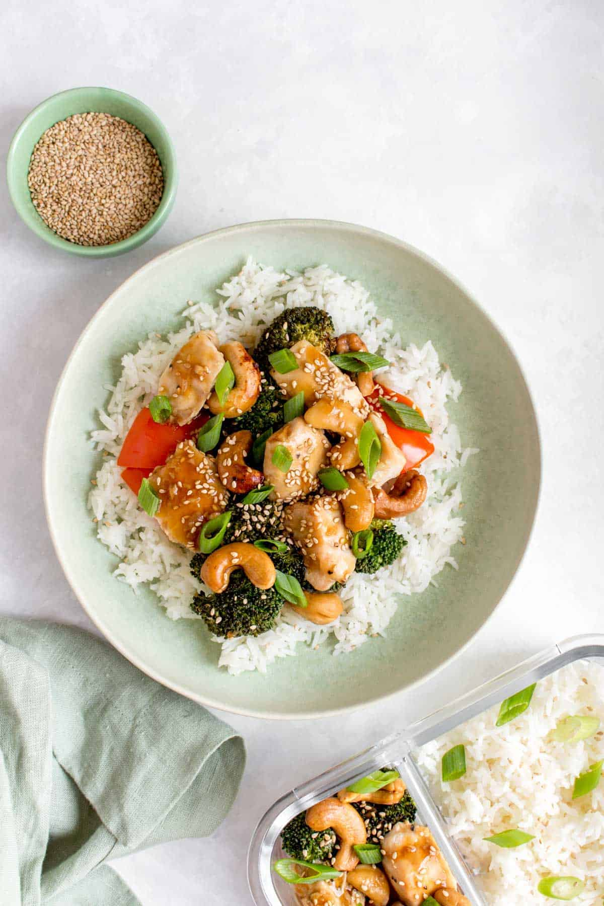 A plate of rice with cashew chicken on top with some sesame seeds on the side and as garnish.