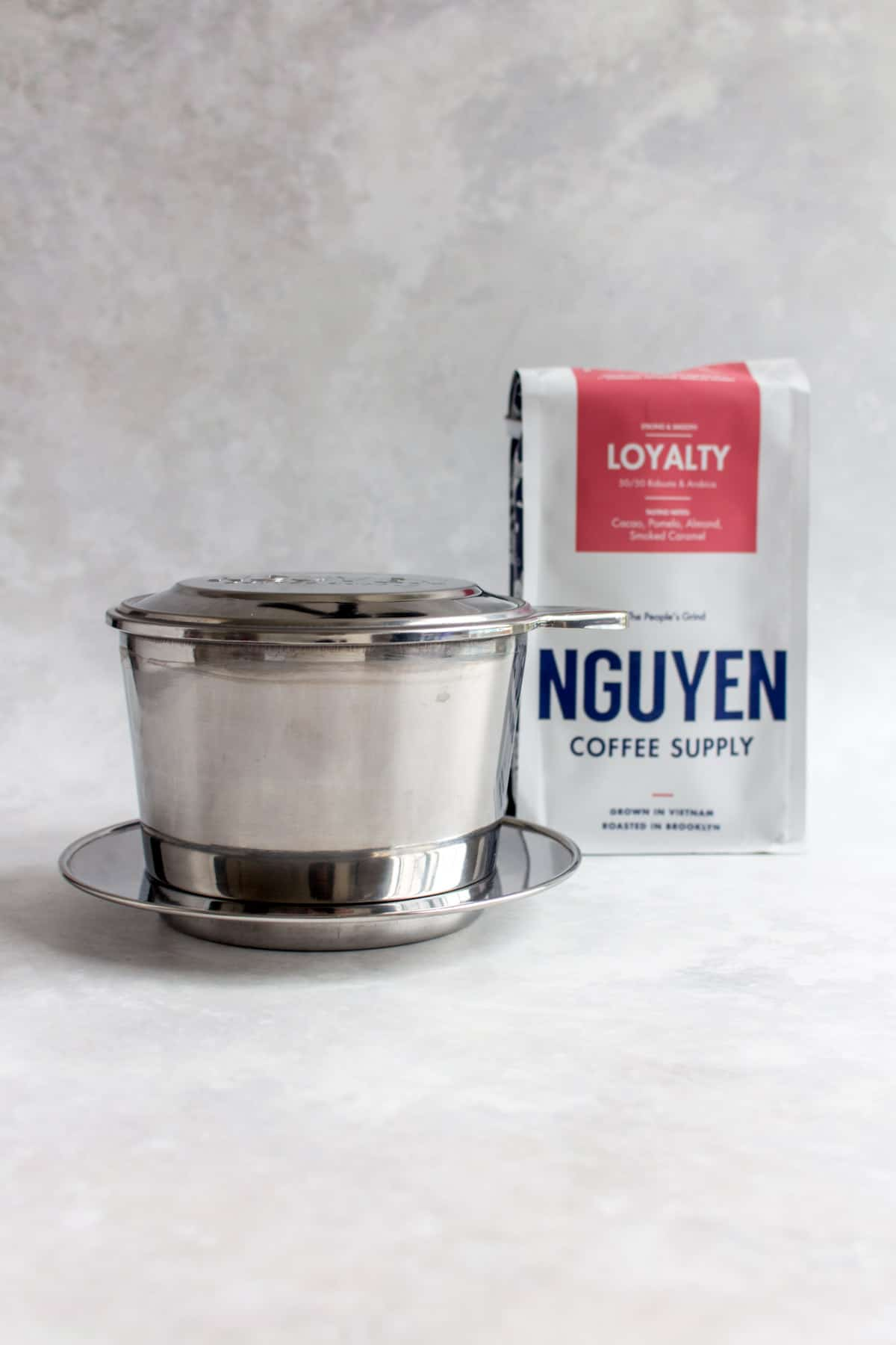 Vietnamese coffee phin with a pack of Nguyen coffee.