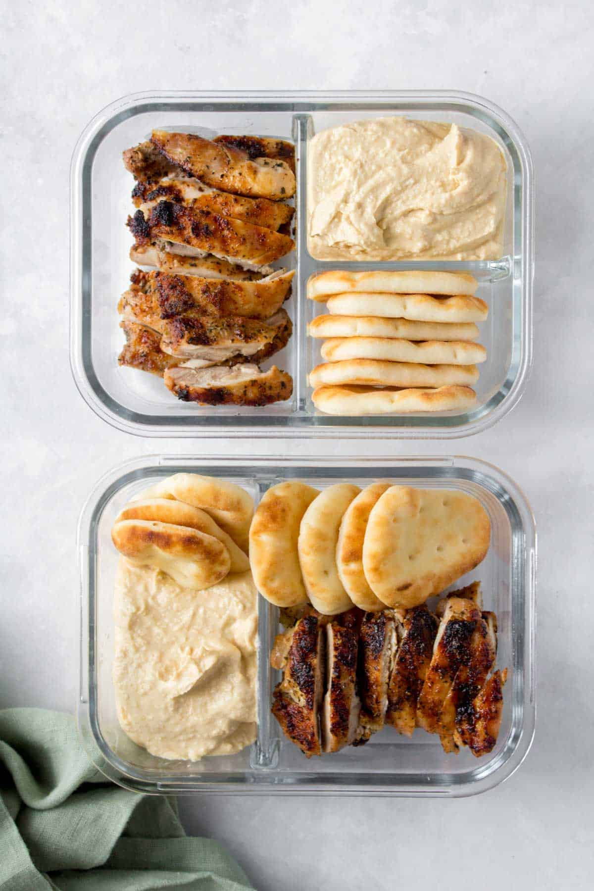 Overhead view of two meal prep containers with sliced chicken thighs, hummus, and mini naans/pitas.